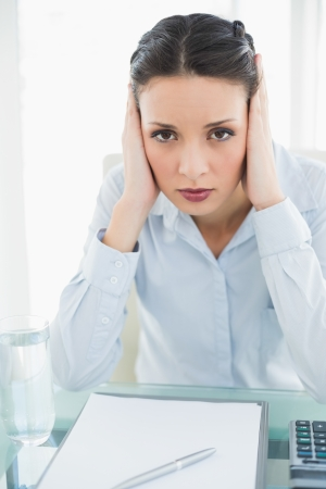 Upset stylish brunette businesswoman holding her head and looking at camera in bright office photo