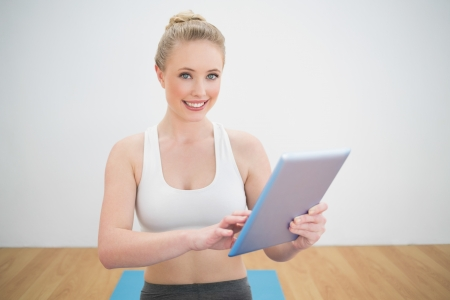 Smiling sporty blonde holding tablet in bright room Stock Photo