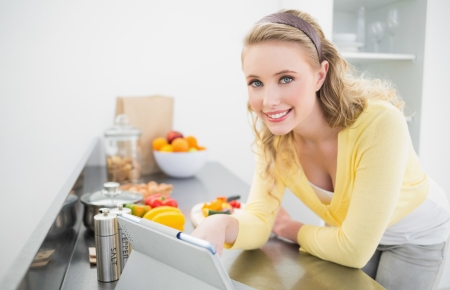 Happy cute blonde using tablet in bright kitchen photo