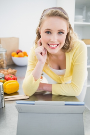 Lucky cute blonde using tablet in bright kitchen photo