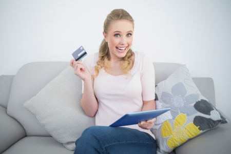 Casual excited blonde holding tablet and credit card in bright living room photo