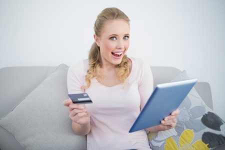 Casual thrilled blonde holding tablet and credit card in bright living room photo
