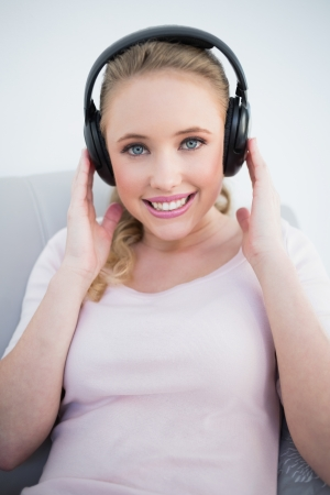 Casual attractive blonde listening to music in bright living room photo