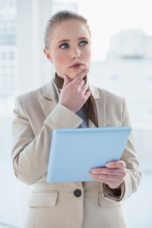 Blonde pensive businesswoman holding tablet in bright office photo