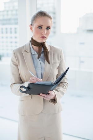 Blonde attractive businesswoman holding a diary in bright office Stock Photo - 25440062