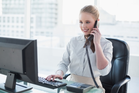 Blonde happy businesswoman phoning at desk in bright office Stock Photo
