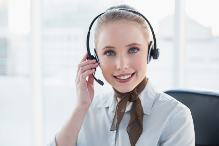 Blonde content businesswoman wearing a headset in bright office photo