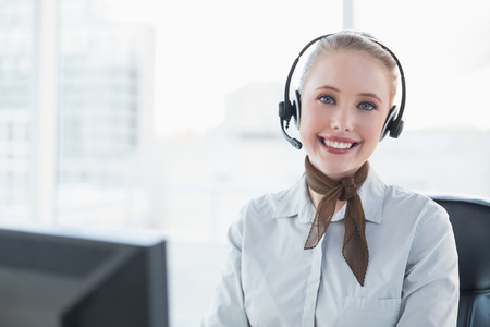 Blonde happy businesswoman wearing a headset in bright office photo
