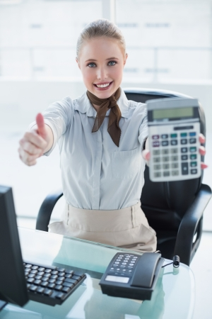 Blonde smiling businesswoman showing calculator and thumb up in bright office photo
