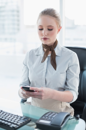 Blonde stern businesswoman using smartphone in bright office Stock Photo