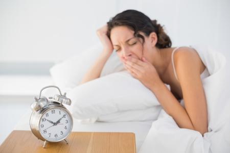 Vermoeide toevallige brunette in witte pyjama's die in haar bed liggen en in heldere slaapkamer geeuwen