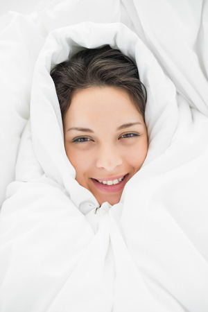 hair wrapped up: Smiling casual brunette wrapped up in her duvet in bright bedroom