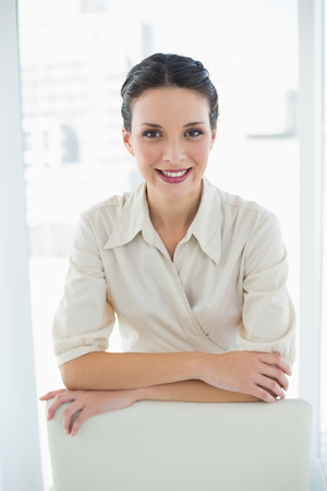 Content stylish brunette businesswoman posing looking at camera in bright office photo