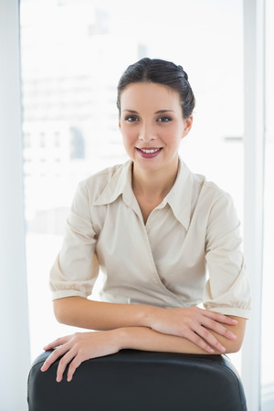 Pleased stylish brunette businesswoman posing looking at camera in bright office photo