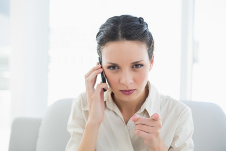 outraged: Irritated stylish brunette businesswoman making a phone call and pointing camera with her finger in bright office