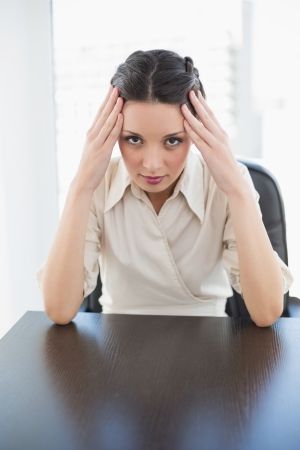 Worried stylish brunette businesswoman holding her head in bright office photo