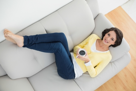 woman relaxing: Relaxed casual brunette in yellow cardigan holding a mug of coffee lying on a couch in bright living room