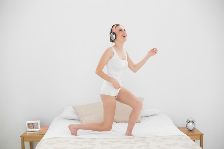 Laughing woman playing air guitar while listening to music and standing on her bed photo