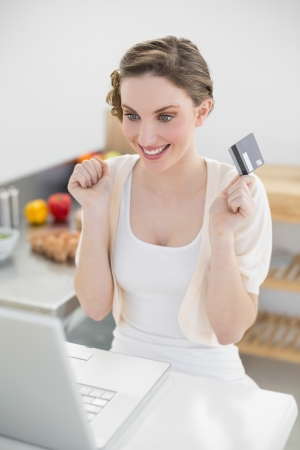 Cheerful attractive woman homeshopping with her notebook sitting in her kitchen photo