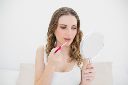 Young woman using lip gloss while looking into a mirror and sitting on her bed photo