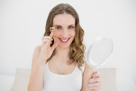 Woman using an eyelash curler while holding a mirror and smiling into the camera photo