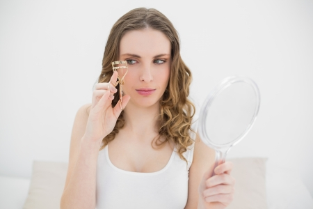 Woman holding an eyelash curler and a mirror while looking at the eyelash curler and sitting on her bed photo