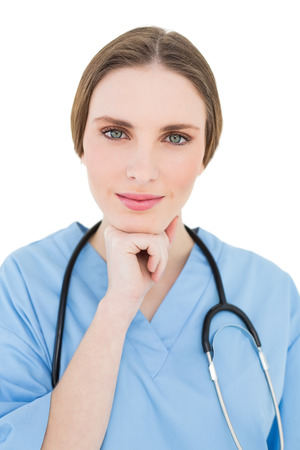 Woman doctor supporting her head with her hand while looking into the camera photo