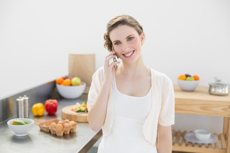 honing: Content young woman honing while standing in kitchen at home