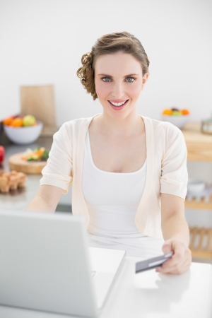 Happy beautiful woman using her notebook for home shopping sitting in kitchen at home photo