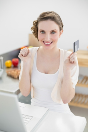 Happy brunette woman sitting in kitchen while home shopping smiling cheerfully at camera photo