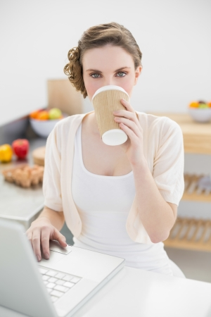 Beautiful woman drinking of disposable cup using her notebook in kitchen at home photo