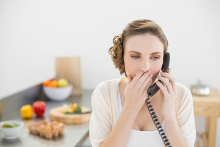 Astonished young woman phoning with her telephone in her kitchen at home photo