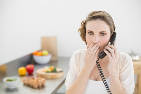 Shocked cute woman phoning in her kitchen with a telephone looking at camera photo
