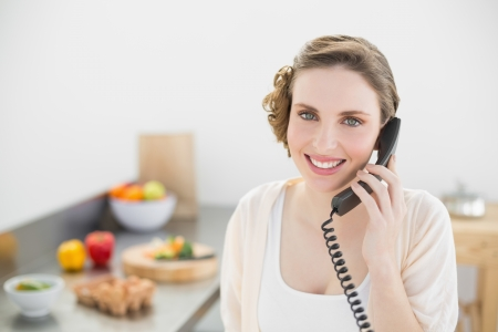 Content beautiful woman phoning in her kitchen with a telephone smiling at camera photo
