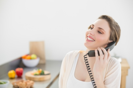 Laughing beautiful woman phoning with a telephone in her kitchen at home photo