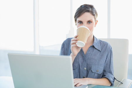 Gorgeous young businesswoman drinking from disposable cup sitting at her desk photo