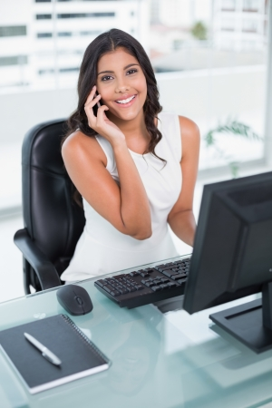 Cheerful cute businesswoman phoning on smartphone in bright office
