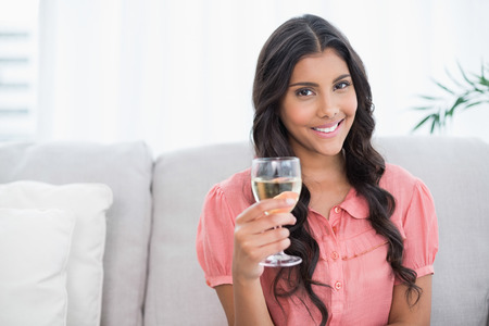 white wine glass: Happy cute brunette sitting on couch holding white wine glass in bright living room Stock Photo