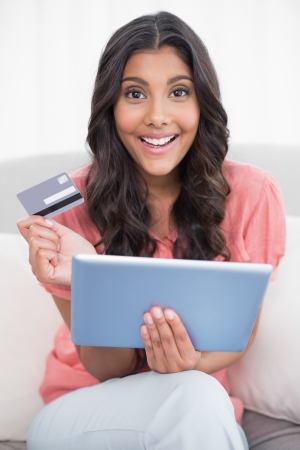 Happy cute brunette sitting on couch holding credit card and tablet in bright living room photo