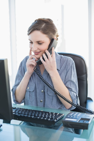 Thinking young businesswoman phoning while sitting a desk in office