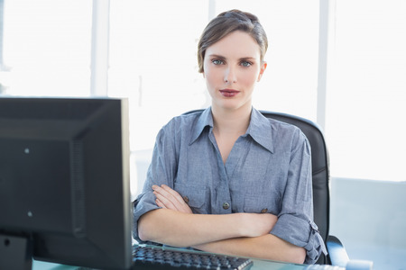 Attractive female businesswoman sitting at her desk with arms crossed looking at camera photo