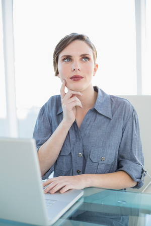 Thoughtful businesswoman using her notebook while sitting at her desk in the office photo