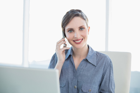 Friendly young secretary phoning with her smartphone sitting at her desk in front of her laptop