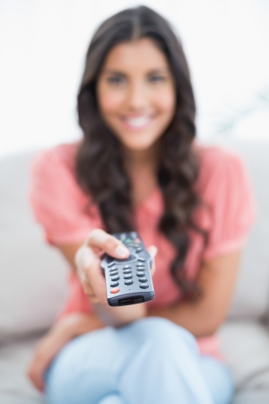 Happy cute brunette sitting on couch holding remote in bright living room photo