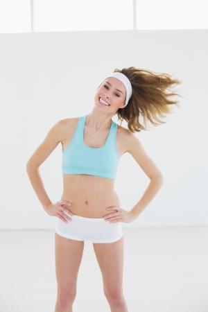 Cheerful slender woman posing in sports hall with hands on hips smiling at camera photo