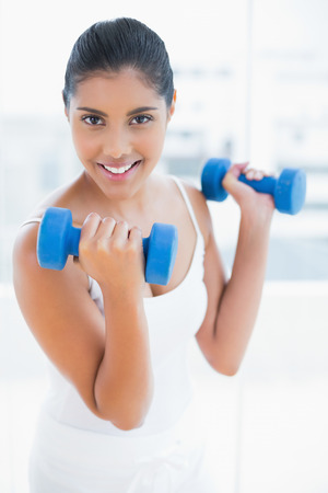 active lifestyle: Smiling toned brunette holding dumbbells in bright room