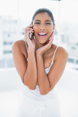 gleeful: Gleeful toned brunette phoning with mobile phone in bright room