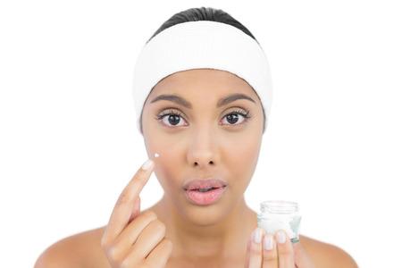 hairband: Shocked  brunette using moisturizer looking at camera on white background Stock Photo