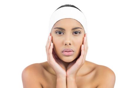 hairband: Unsmiling  brunette with hairband touching face on white background