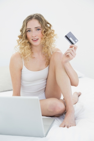 Pretty happy blonde sitting on bed using laptop and credit card in bright bedroom photo